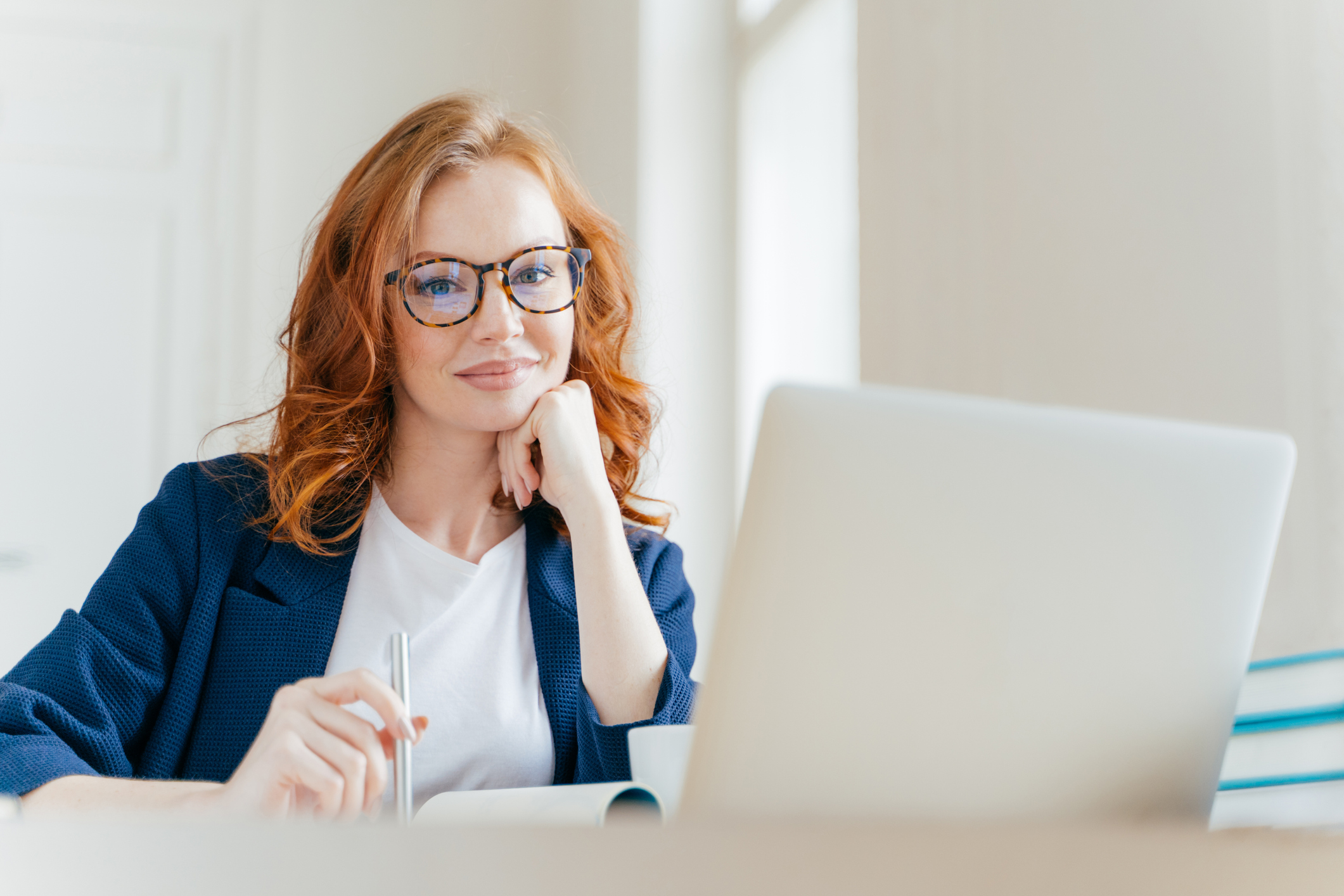 Horizontal shot of pleasant looking successful professional female lawyer learns clients case, works on modern laptop computer, dressed in formal apparel and transparent glasses, poses in office